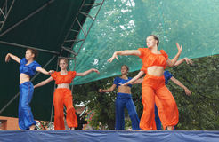 Le ragazze in vestito luminoso ballano e mostrano le acrobazie acrobatiche su Sc Immagini Stock Libere da Diritti