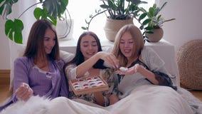 Le ragazze weekend, giovani donne in vestaglie di seta riposano sul letto con una scatola di caramelle dolci nella sala video d archivio
