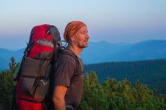 Le randonneur avec le sac à dos examine la distance Images stock