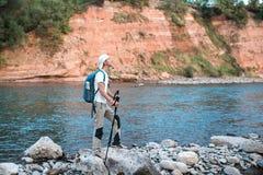 Le randonneur avec le sac à dos bleu admire la nature images libres de droits