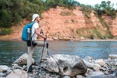 Le randonneur avec le sac à dos bleu admire la nature photos libres de droits