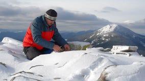 Le randonneur commence le feu dans les montagnes neigeuses banque de vidéos