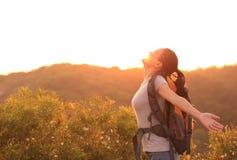 Le randonneur de femme élevé arme le dessus de montagne Photographie stock libre de droits