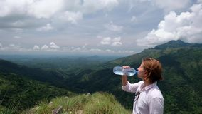 Le randonneur de femme apprécient la vue buvant l'eau froide banque de vidéos