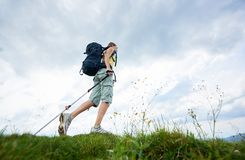 Le randonneur de femme trimardant sur la colline herbeuse, sac ? dos de port, utilisant le trekking colle dans les montagnes photos stock
