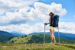 Le randonneur de femme trimardant sur la colline herbeuse, sac ? dos de port, utilisant le trekking colle dans les montagnes photo stock