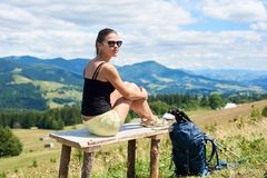 Le randonneur de femme trimardant sur la colline herbeuse, sac ? dos de port, utilisant le trekking colle dans les montagnes image stock
