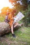 Le randonneur de femmes avec le sac à dos vérifie la carte Photographie stock