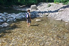 Le randonneur de petit garçon croise le gué de crique de montagne Photos libres de droits