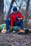 Le randonneur de sourire grille les saucisses au feu de camp et joue avec Photographie stock