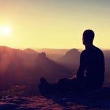 Le randonneur de Sportsmann dans les vêtements de sport noirs s'asseyent sur le dessus de montagne et prennent à un repos la mont Photo stock