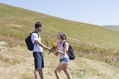 Le randonneur donne des fleurs à une femme en voyage de hausse Image libre de droits