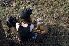Le randonneur et le chien femelles prennent le repos sous l'arbre dans la forêt Photographie stock libre de droits