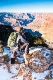 Le randonneur examine la profondeur de Grand Canyon avant d'aller sur la traînée Image libre de droits