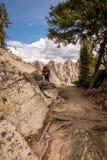 Le randonneur fait une pause pour apprécier la vue à partir des dessus de haute montagne Photographie stock libre de droits