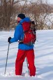 Le randonneur, homme marche par la forêt dans la neige profonde Image stock