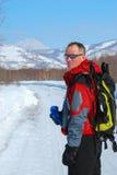 Le randonneur marche le long de la route dans la forêt d'hiver Photos stock