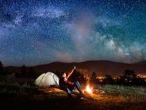 Le randonneur masculin montre son amant dans le ciel étoilé Photo stock