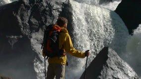 Le randonneur observe une cascade dans le mouvement lent banque de vidéos
