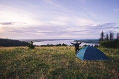 Le randonneur rencontre bonjour avec les mains augmentées juste sorties de sa tente Photo libre de droits