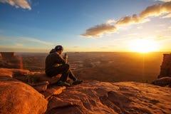 Le randonneur rencontre le coucher du soleil au point de vue grand en parc national de Canyonlands en Utah, Etats-Unis photos stock