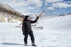Le randonneur reste sur une colline de montagne de neige et apprécie la belle vue Photographie stock