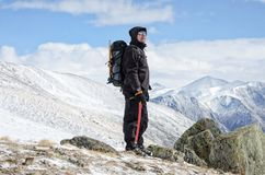 Le randonneur reste sur une colline de montagne de neige et apprécie la belle vue Photographie stock libre de droits