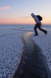 Le randonneur sautant par-dessus une fissure en glace Images stock