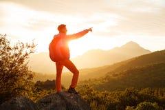 Le randonneur se tient sur la falaise au-dessus du lever de soleil Photo stock