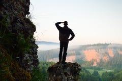 Le randonneur se tient sur le lever de soleil de montagne Image stock