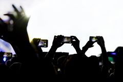 Le rassemblement de la mémoire numérique desserre la capacité d'être présent, ombre des personnes avec des téléphones portables images libres de droits