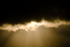 Le rayon de Sun par les nuages foncés Photo stock