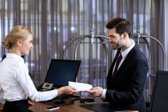 le receptionisten som ger kuvertet till affärsmannen royaltyfri bild
