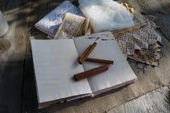 Le recette-livre ouvert avec des bâtons de cannelle et le vintage lacent dessus Images libres de droits