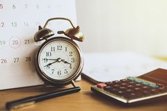 Le recouvrement des dettes et l'impôt assaisonnent le concept avec l'échéance sur le calendrier avec le réveil et la calculatrice photographie stock libre de droits