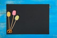 Le rectangle noir avec des sucreries sur un fond en bois bleu Photo stock