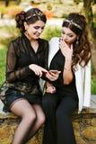 Le regard d'ami au téléphone et discutent quelque chose Rire et sourire, devenant fou, ayant l'amusement Jeune femme élégante à Photographie stock libre de droits