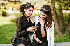 Le regard d'ami au téléphone et discutent quelque chose Rire et sourire, devenant fou, ayant l'amusement Jeune femme élégante à Image stock