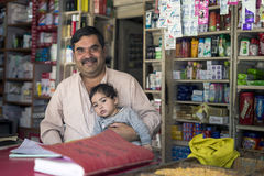 Le regard d'homme d'affaires dans le sourire avant, tiennent son nourrisson, se reposent à l'épicerie Images libres de droits