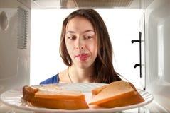Le regard de fille sur les broads de beurre et lèchent. photographie stock libre de droits