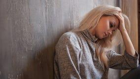 Le regard du femme fille blonde s'asseyant sur le plancher, la tristesse et la dépression photo stock
