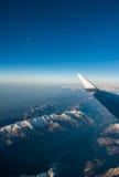 Le regard par les avions de fenêtre pendant le vol une neige a couvert l'italien et l'Osterreich Photos stock
