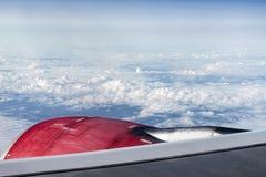 Le regard rouge de turbine de moteur à réaction par la fenêtre d'avions sur le ciel bleu de jour ensoleillé opacifie Photos libres de droits