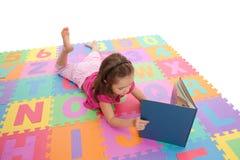 Le relevé d'enfant de fille badine le livre sur le couvre-tapis d'alphabet Images stock