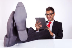 Le relevé d'homme d'affaires sur sa garniture électronique de tablette Image libre de droits