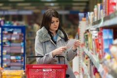 Le relevé de femme sa liste d'achats dans le supermarché Photos stock