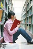 Le relevé de jeune femme dans la bibliothèque Images libres de droits