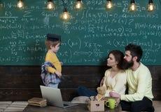 Le relevé de maman avec le fils Petit enfant apprenant à la maison avec des parents Étude à la maison avec amour L'étude à la mai Photo stock