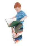 Le relevé de garçon badine le livre sur la pile des livres Image stock