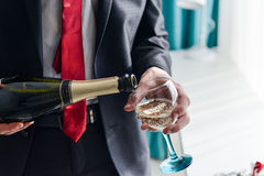 Le remplissage d'homme a décoré le verre avec le champagne Image libre de droits